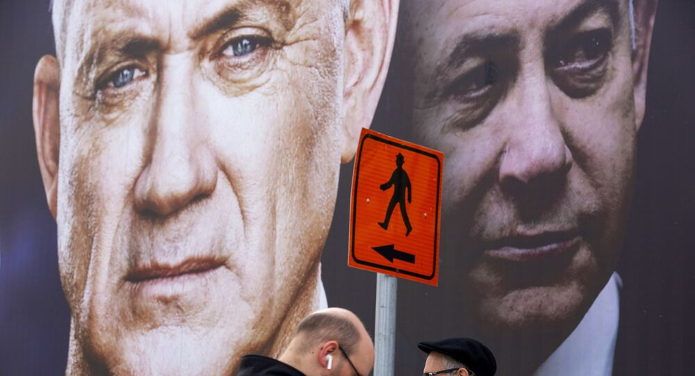 People walk past an election campaign billboard for the Blue and White party, the opposition party led by Benny Gantz, left, in Ramat Gan, Israel, Sunday, Feb. 23, 2020. Prime Minister Benjamin Netanyahu of the Likud party is pictured at right.