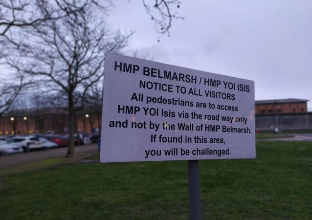 Belmarsh Prison sign with Belmarsh prison behind it out of focus