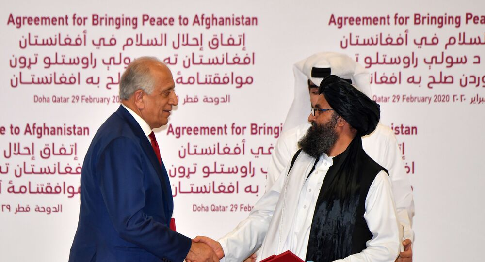 US Special Representative for Afghanistan Reconciliation Zalmay Khalilzad and Taliban co-founder Mullah Abdul Ghani Baradar shake hands after signing a peace agreement during a ceremony in the Qatari capital Doha on February 29, 2020