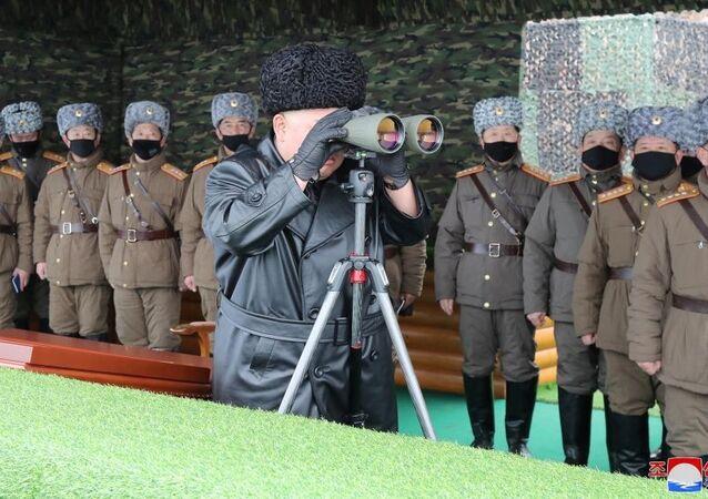 North Korean leader Kim Jong-un looks into binoculars during a missile test.