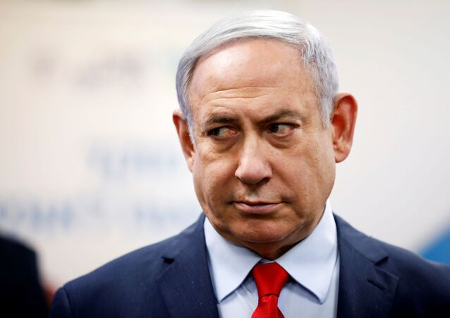 Israeli Prime Minister Benjamin Netanyahu looks on as he delivers a statement during his visit at the Health Ministry national hotline, in Kiryat Malachi, Israel
