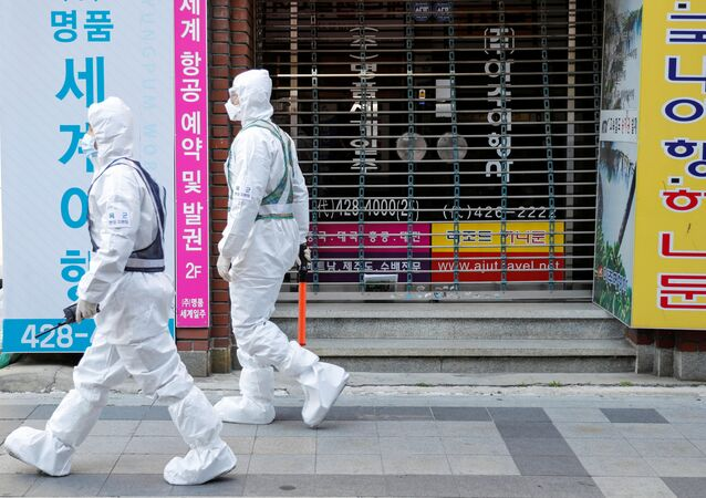 South Korean soldiers wearing protective gear walk past a closed shop while they sanitize a street after the rapid rise in confirmed cases of the novel coronavirus disease of COVID-19 in Daegu, South Korea March 2, 2020