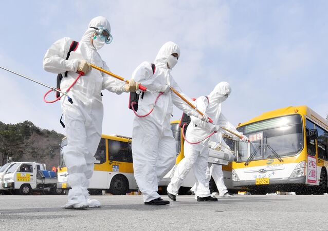 Employees from a disinfection service company sanitise a bus garage in Gwangju, South Korea, 3 March 2020.