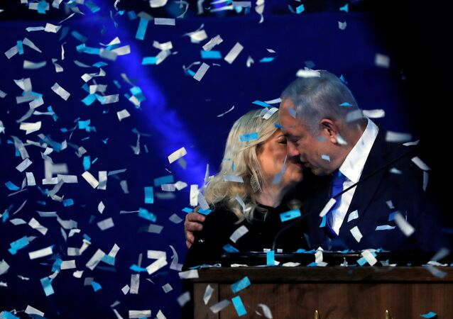 Confetti falls as Israeli Prime Minister Benjamin Netanyahu kisses his wife Sara after speaking to supporters following the announcement of exit polls in Israel's election at his Likud party headquarters in Tel Aviv, Israel March 3, 2020.