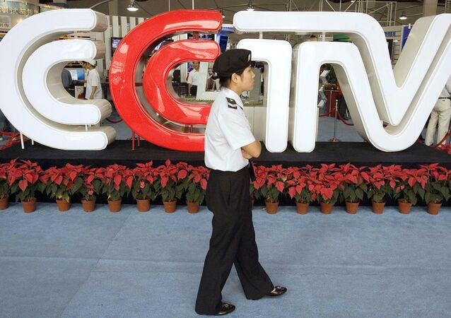 Chinese security personnel walks past the logo for China Central Television (File)