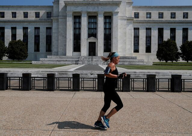 A woman jogs past the Federal Reserve building in Washington, U.S., July 16, 2018