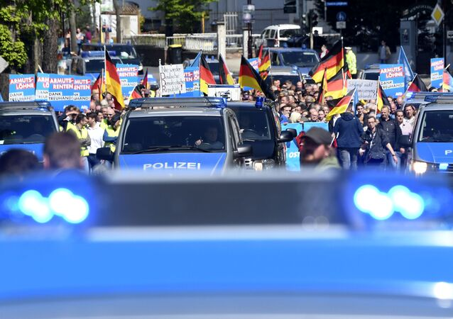 AfD supporters walk accompanied by police cars in Erfurt, Germany, Wednesday, May 1, 2019. The Alternative for Germany launches its European parliament election campaign in the eastern city of Erfurt.