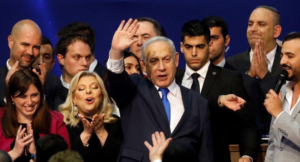 Israeli Prime Minister Benjamin Netanyahu stands next to his wife Sara as he waves to supporters following the announcement of exit polls in Israel's election at his Likud party headquarters in Tel Aviv, Israel March 3, 2020.