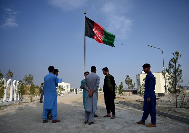 Afghanistan's national flag flutters as youths stand at Wazir Akbar Khan hilltop overlooking Kabul on September 29, 2019