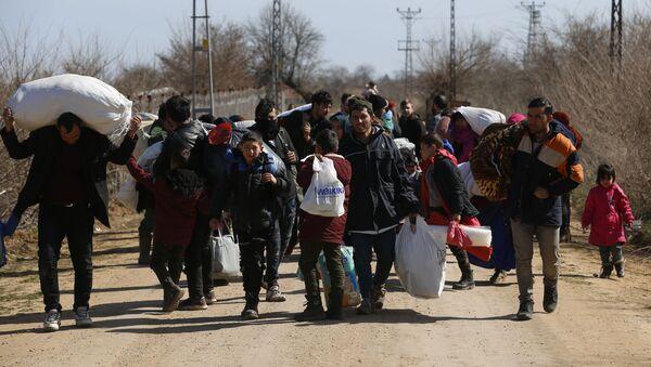 Migrants carrying their belongings walk near the Pazarkule gate in Edirne region, at the Turkish-Greek border on Tuesday, March 3, 2020 - Sputnik International