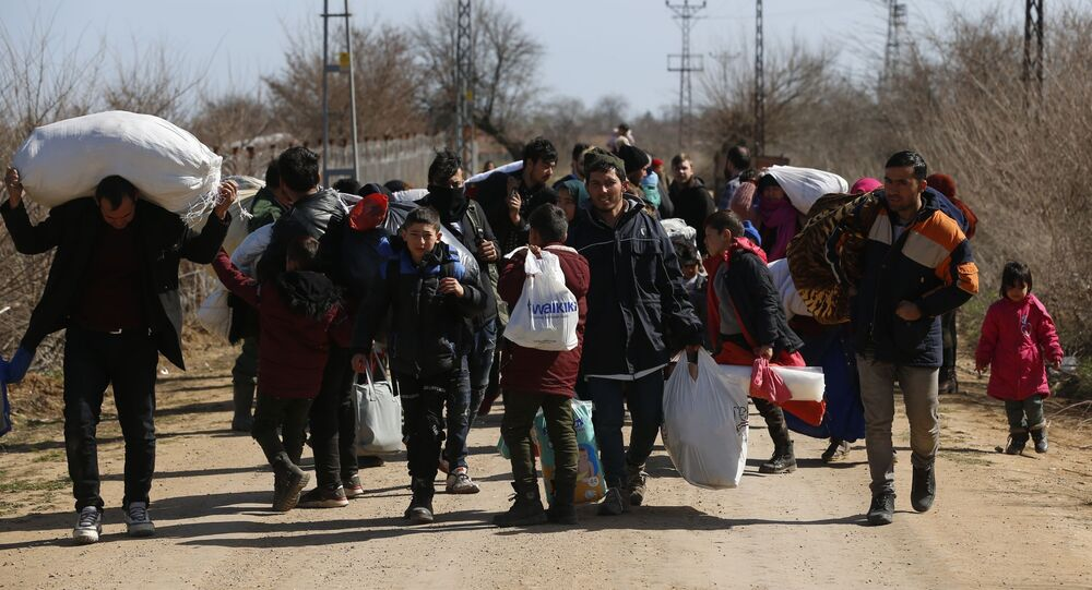 Migrants carrying their belongings walk near the Pazarkule gate in Edirne region, at the Turkish-Greek border on Tuesday, March 3, 2020