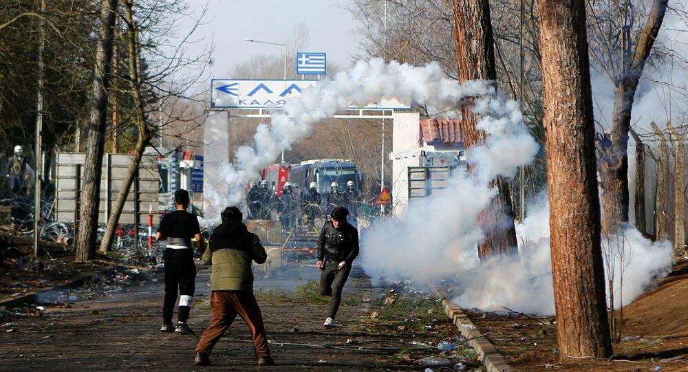 A migrant runs away from tear gas at Turkey's Pazarkule border crossing with Greece's Kastanies, near Edirne, Turkey, March 2, 2020