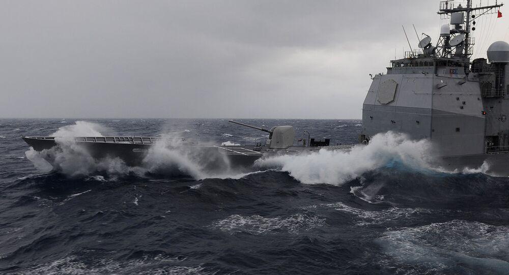 Waves break over the USS Bunker Hill