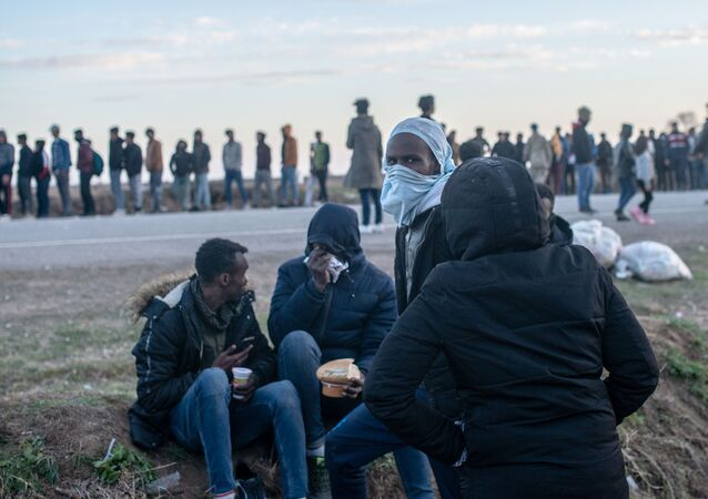 Migrants wait for a food distribution in front of the Pazarkule border crossing to Greece, on March 3, 2020, at Pzarkule in Edirne.