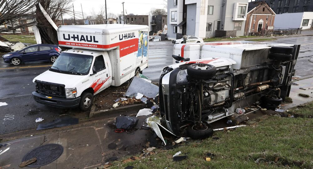 Damaged trucks sit on a sidewalk as well as the street following a deadly tornado, Tuesday, March 3, 2020, in Nashville, Tenn. Tornadoes ripped across Tennessee early Tuesday, shredding buildings and killing multiple people.