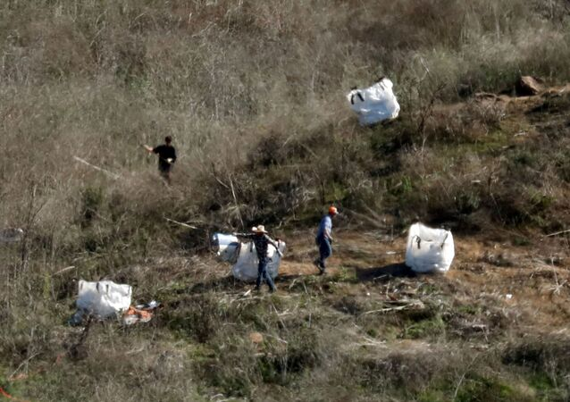Personnel collect debris while working with investigators at the helicopter crash site of NBA star Kobe Bryant in Calabasas, California