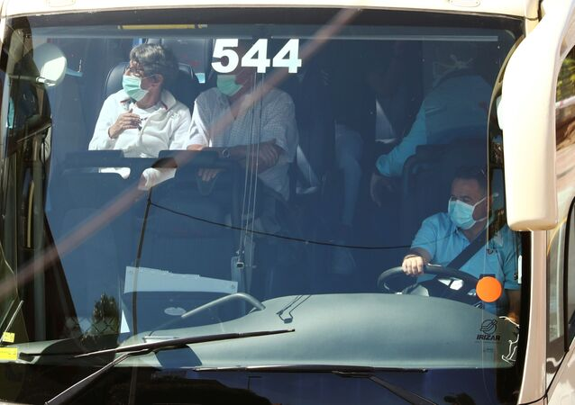 Tourists, wearing protective face masks, sit in a bus as they leave the H10 Costa Adeje Palace hotel, which is on lockdown after the novel coronavirus has been confirmed in Adeje, in the Spanish Canary Island of Tenerife, Spain, March 3, 2020