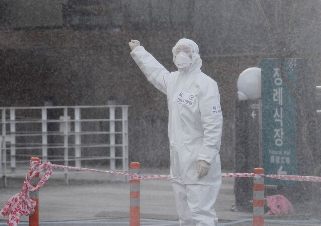 A South Korean solider in protective gear gives a sign to his colleague as they spray disinfectant on visiting cars at a 'drive-thru' testing center for the novel coronavirus disease of COVID-19 in Yeungnam University Medical Center in Daegu