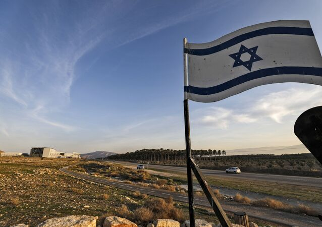 An Israeli flag hovers cars driving by the Israeli settlement of Shlomtzion in the Jordan valley in the occupied West Bank on January 27, 2020.