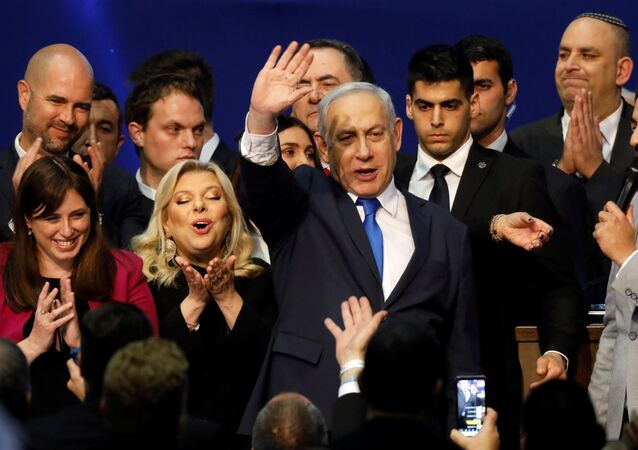 Israeli Prime Minister Benjamin Netanyahu stands next to his wife Sara as he waves to supporters following the announcement of exit polls in Israel's election at his Likud party headquarters in Tel Aviv, Israel March 3, 2020