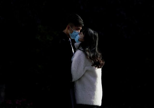 A couple wearing masks kiss at a main shopping area, in downtown Shanghai, China, as the country is hit by an outbreak of a new coronavirus, February 16, 2020