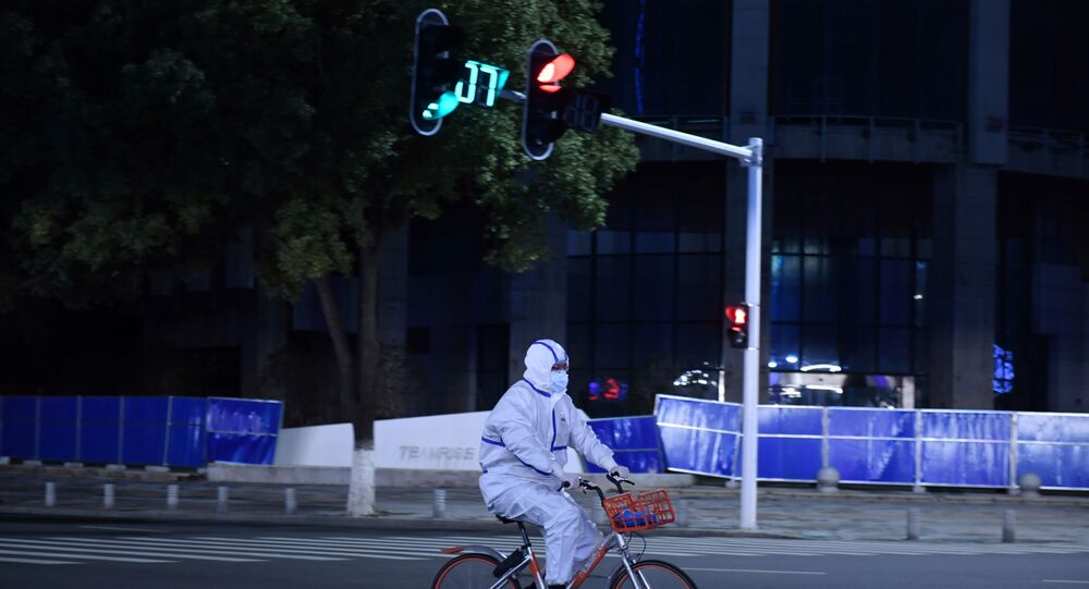 A man in a protective suit rides a shared bicycle at an intersection in Wuhan, the epicentre of the novel coronavirus outbreak, Hubei province, China March 4, 2020