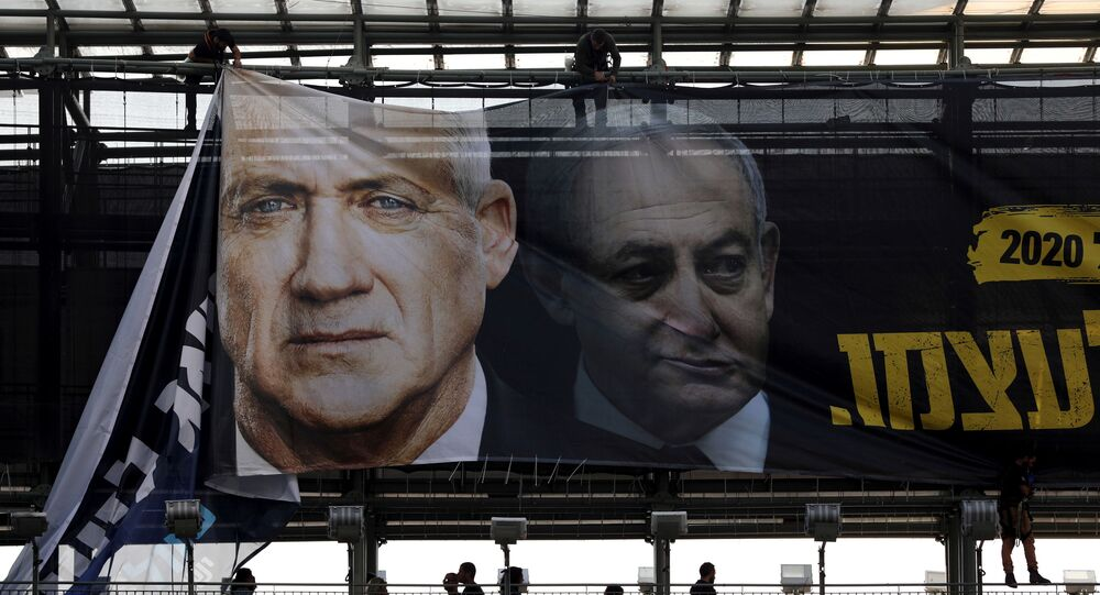 Labourers hang a banner depicting Benny Gantz, leader of Blue and White party, and Israel Prime minister Benjamin Netanyahu, as part of the party's campaign ahead of the upcoming election, in Tel Aviv, Israel February 17, 2020.