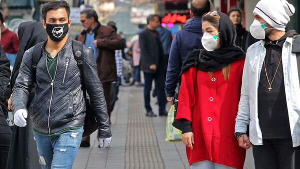 A man wears a protective mask bearing the logo of the US' National Aeronautics and Space Administration (NASA) while walking with others also wearing masks along a street in the Iranian capital Tehran on February 24, 2020 - Sputnik International