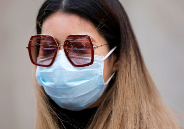 A woman in a face mask walks in the downtown area of Manhattan, New York City, after further cases of coronavirus were confirmed in New York, U.S., March 5, 2020