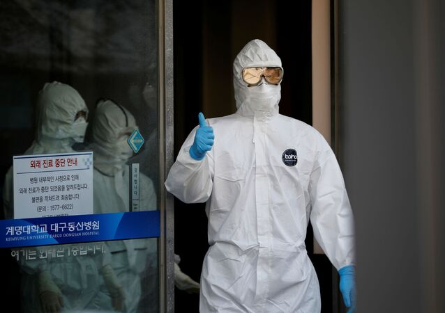 A medical worker gives a thumbs-up to media as he walks out of a facility where coronavirus disease (COVID-19) patients receive treatment at Keimyung University Dongsan Medical Center in Daegu, South Korea, March 5, 2020