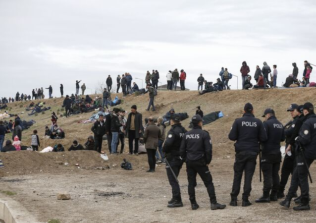 Turkish police stand by migrants camping in Edirne near the Turkish-Greek border