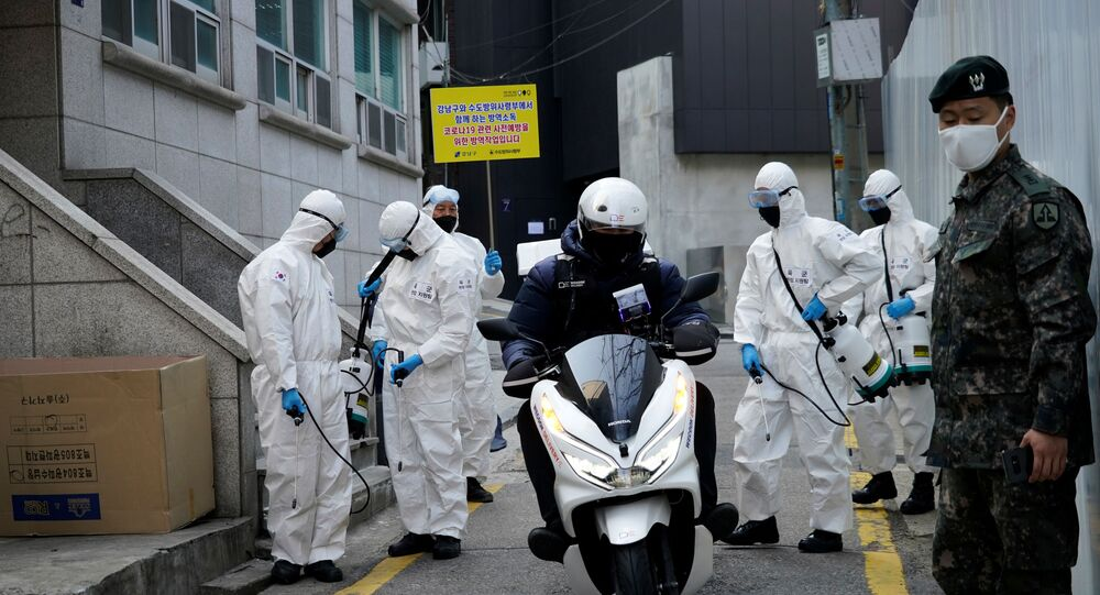 South Korean soldiers in protective gear sanitize a street at a shopping district in Seoul, South Korea, March 6, 2020