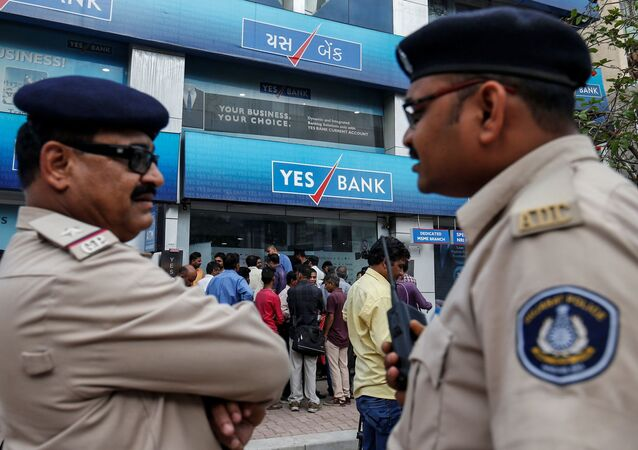 Policemen stand guard as people wait outside a Yes Bank branch to withdraw their money in Ahmedabad, India, March 6, 2020