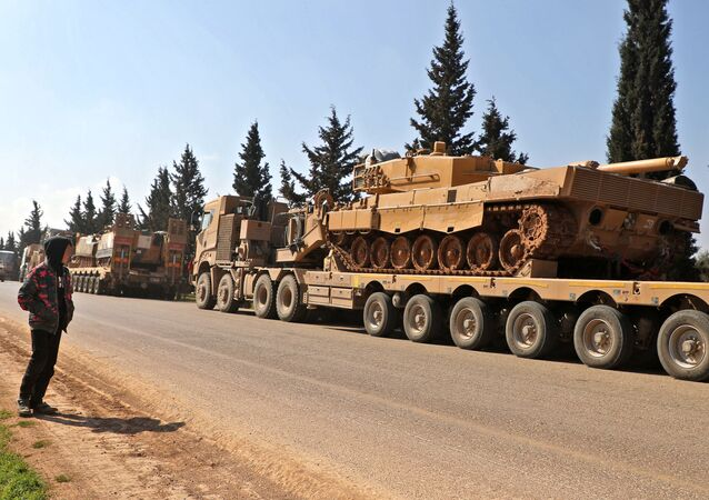 A boy looks at a convoy of Turkish military vehicles near the town of Hazano in the rebel-held northern countryside of Syria's Idlib province on March 3, 2020.