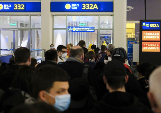 In this 2 February 2020 file photo, evacuees board an evacuation flight for EU nationals at Wuhan Tianhe International Airport in Wuhan in central China's Hubei Province. Arek and Jenina Rataj were starting a new life in the Chinese industrial centre of Wuhan when a viral outbreak spread across the city of 11 million. While they were relatively safe sheltering at home, Arek felt compelled to go out and document the outbreak of the new type of coronavirus. Among his subjects: the construction of a new hospital built in a handful of days; biosecurity check points; and empty streets.