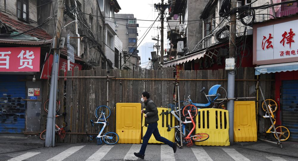 A man wearing a face mask runs past a street blocked by barricades and shared bicycles in Wuhan, the epicentre of the novel coronavirus outbreak, Hubei province, China March 5, 2020