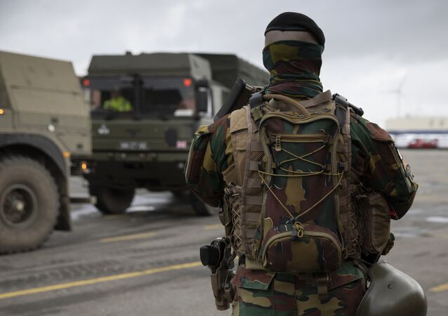 A Belgian solider patrols in a temporary military zone as vehicles arrive from a British naval vessel, taking part in U.S.-led war games, at the Port of Antwerp in Antwerp, Belgium, Monday Feb. 3, 2020. The Defender-Europe 2020 exercises will involve approximately 20,000 American troops; the biggest deployment of U.S.-based soldiers to Europe in 25 years.