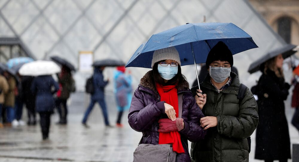 Tourists wearing masks walk away from the Louvre