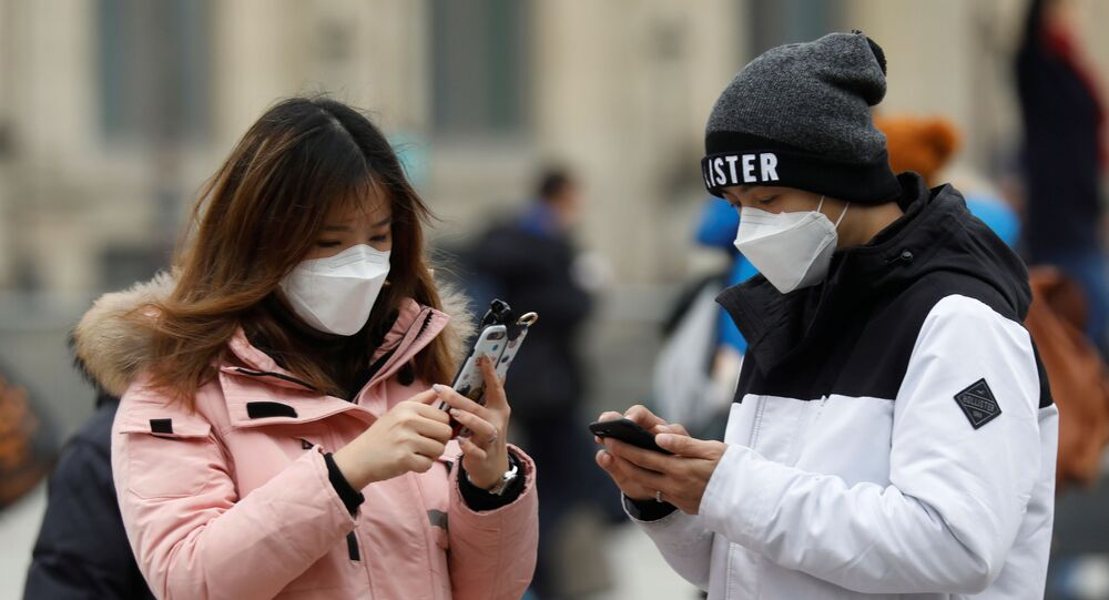 A couple wearing masks check their mobile phones