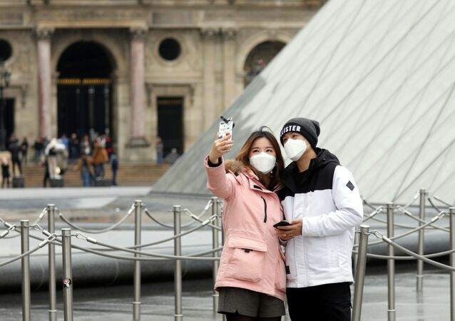 A couple wearing masks poses for a selfie near the Louvre Pyramid in Paris