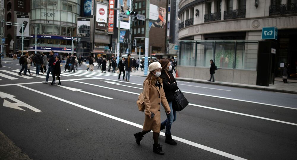 Women, wearing protective face masks walk in Tokyo