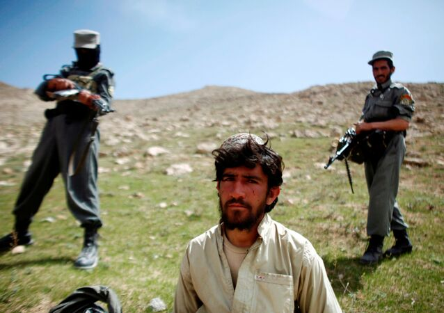 Afghan policemen stand next to a captured Taliban fighter after a gun battle near the village of Shajoy in Zabol province, Afghanistan March 22, 2008.