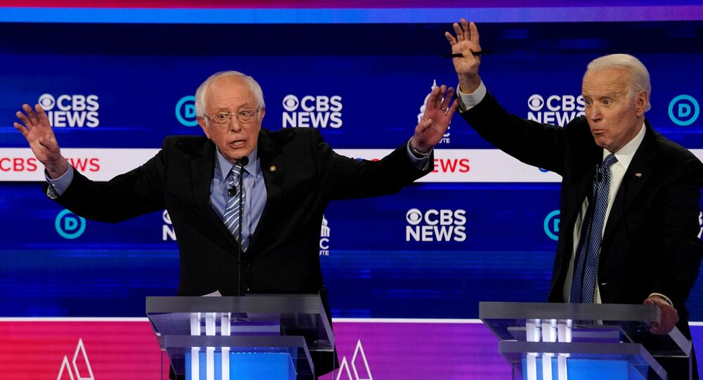 Democratic 2020 U.S. presidential candidates Senator Bernie Sanders and former Vice President Joe Biden brush hands as they have an exchange in the tenth Democratic 2020 presidential debate at the Gaillard Center in Charleston, South Carolina, U.S. February 25, 2020.
