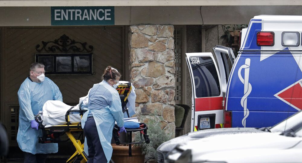 Ambulance workers move a man on a stretcher from the Life Care Centre in Kirkland, Washington into an ambulance