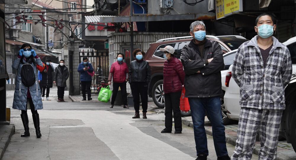 Residents line up to collect vegetables purchased through group orders at a residential area in Wuhan, the epicentre of the novel coronavirus outbreak, Hubei province, China March 5, 2020