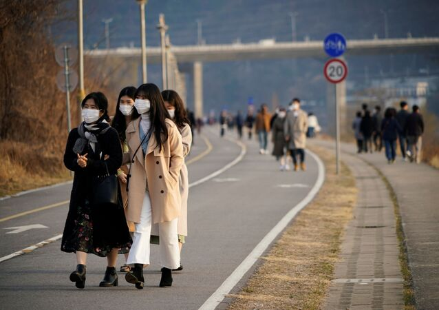 Women wearing masks to prevent contracting the coronavirus take a walk at a Han River park in Namyangju, South Korea March 7, 2020