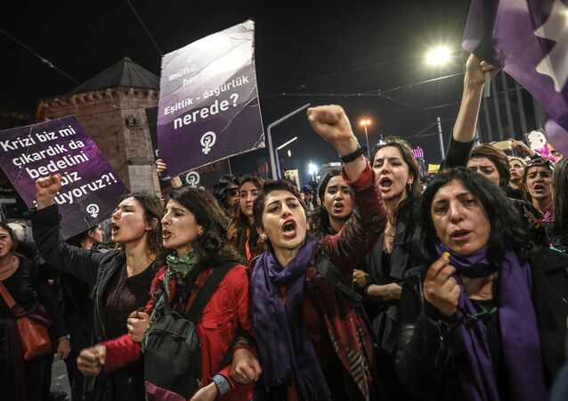 Women shout slogans as Turkish anti-riot police officers try to push them back during a rally marking International Women's Day on Istiklal avenue in Istanbul on March 8, 2019.