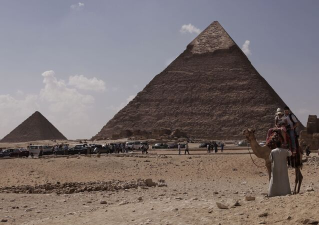 Tourists ride a camel as they visit the historical site of the Giza Pyramids, in front of the Khafre pyramid, right, near Cairo, Egypt. File photo.