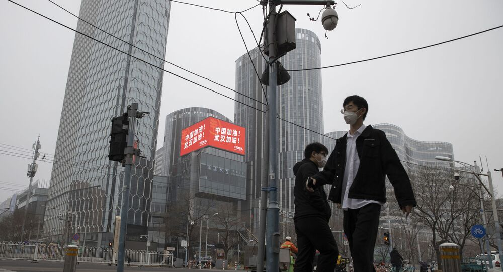 Residents walk past a retail and office district with a screen showing propaganda which reads Go China! Go Wuhan as businesses slowly restart in Beijing on Sunday, March 8, 2020. As China's coronavirus cases and death steadily falls, authorities are trying to restart its businesses and factories after a virtual shutdown which has had a ripple effect affecting the global economy.