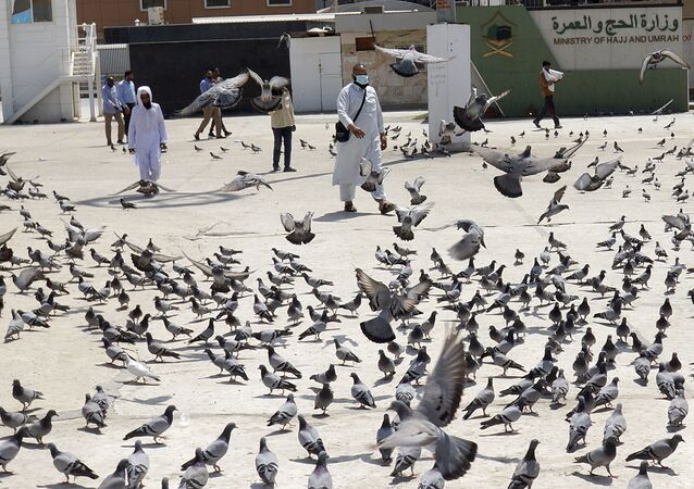 A Muslim worshipper walks past pigeons after the noon prayers outside the Grand Mosque, in the Muslim holy city of Mecca, Saudi Arabia, Saturday, March 7, 2020. Saudi Arabia announced there would be no spectators for sports competitions and games starting Saturday in order to combat the spread of the virus. The kingdom has taken unprecedented measures against the virus' spread, including halting all pilgrimage in Mecca, Islam's holiest site.